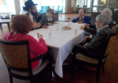 Our residents engaging in conversation with Rabbi Marshall, who visits every Friday for our Shabbat Program.